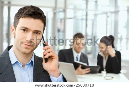 Young smiling businessman calling on phone, business meeting at background.