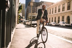 Young smiling businessman going to work by bike. Man in suit riding bicycle on sidewalk in morning.