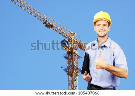 Young smiling businessman in his helmet against the backdrop of the building under construction