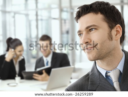 Young smiling businessman on business meeting.