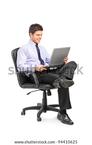 Young smiling businessman sitting in office chair and working on laptop computer isolated on white background