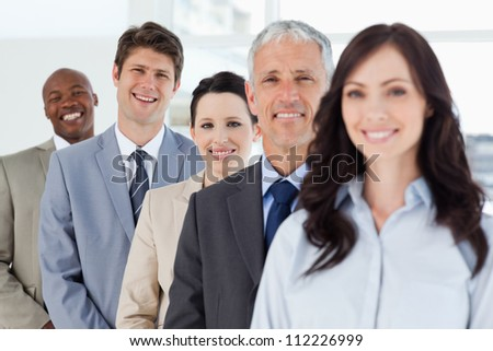 Young smiling businessman standing in a well-lit room among his co-workers #112226999