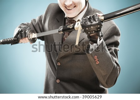 Young smiling businessman with sword in his arms ready to fight with rivals and to win. Business is a struggle concept, looking in the future with optimism concept.