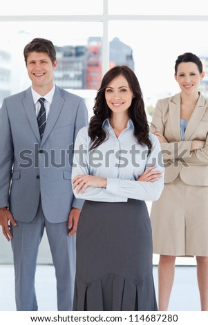 Young smiling businesswoman crossing her arms in front of two relaxed colleagues