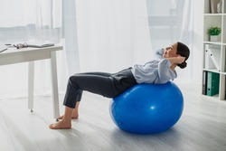 young smiling businesswoman doing abs on fitness balls in office