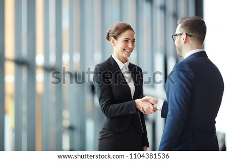 Young smiling businesswoman giving handshake to foreign business partner at meeting