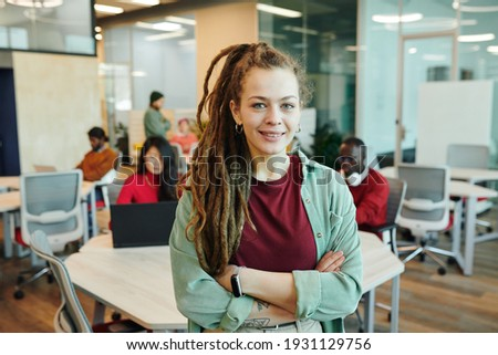 Young smiling businesswoman or designer in casualwear crossing her arms by chest while standing in front of camera in working environment Photo stock ©