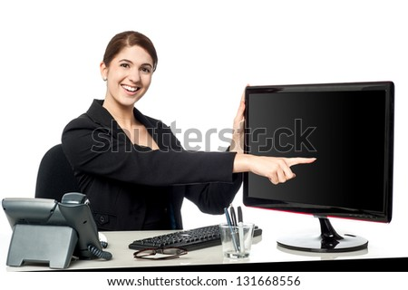 Young smiling businesswoman pointing at blank computer screen.