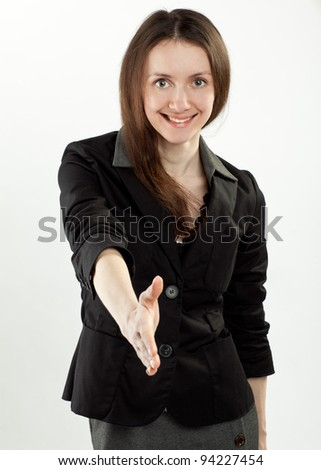 Young smiling businesswoman reaching out hand for handshake illustrating business offer; studio shot on neutral background