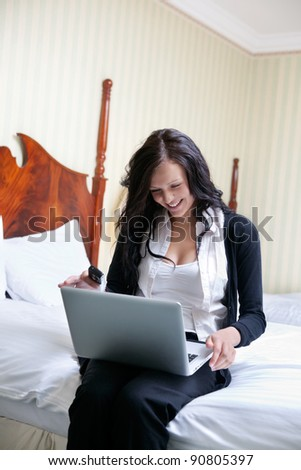 Young smiling businesswoman using laptop while sitting on bed - stock photo