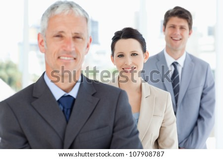 Young smiling businesswoman wearing a formal suit between two executives