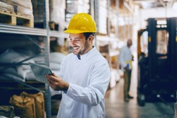 Young smiling Caucasian auditor in white uniform and with yellow helmet on head using tablet for checking on goods in warehouse. In background worker standing next to forklift.