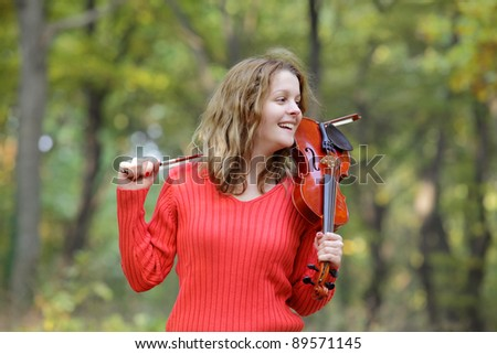 Young smiling Caucasian girl in  forest with violin
