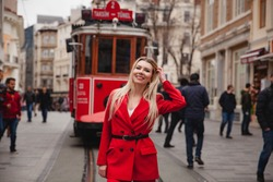 Young smiling Caucasian tourist woman staying in front of red tramway on Istiklal street in Beyoglu, Istanbul/Turkey.