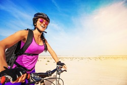 young smiling caucasian woman with a backpack riding bike in desert