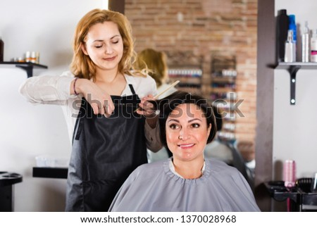 Young smiling cheerful positive hairdresser does to woman haircut with use of scissors and hairbrushes in hairdress salon