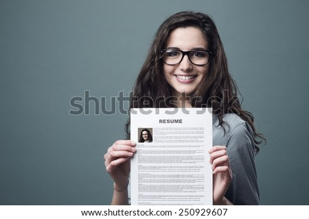 Young smiling cheerful woman holding her resume
