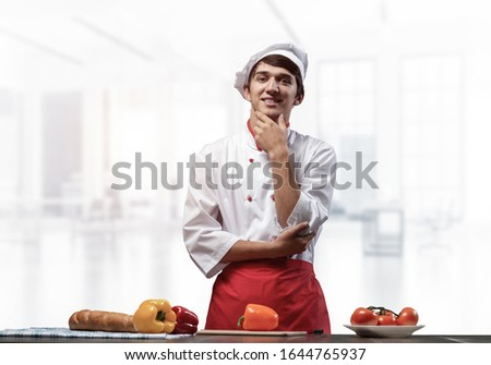 Young smiling chef standing near cooking table with fresh vegetables. Pleased chef in white hat and red apron in light kitchen interior. Cooking classes advertising. Restaurant food preparation Stock photo ©