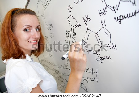 Young smiling chemist student writing formulas. Cute and smart