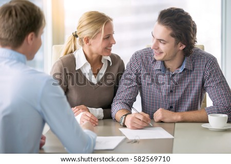 Young smiling couple about to sign a house renting agreement, happy to buy new apartment, meeting in the office with a trusted, reliable real estate agent, confident in credit