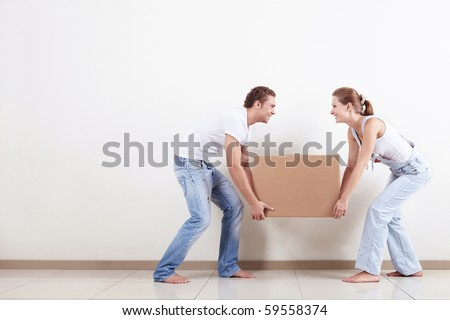 Young smiling couple carries a box