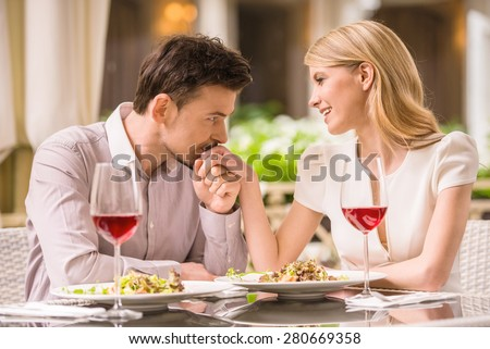 Young smiling couple enjoying the meal in gorgeous restaurant and drinking wine. Man kissing woman\'s hand.