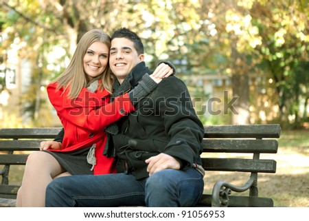 young smiling couple in love embracing in park