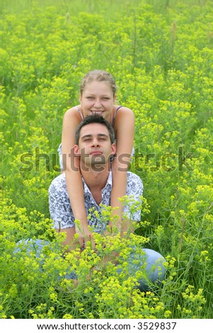 Young smiling couple in the green grass field, portrait orientation