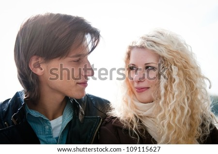 Young smiling couple looking on each other  - outdoor lifestyle portrait
