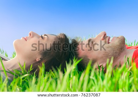 Young smiling couple lying down on the grass and dreaming at their future