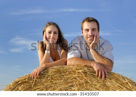 young smiling couple lying on a straw bale looking at the camera