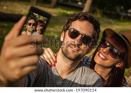 Young Smiling Couple Making A Self Portrait With Smart Phone. Focus Is On Couple.