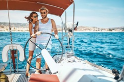 Young smiling couple on a sailing boat -Romantic vacation and luxury travel.