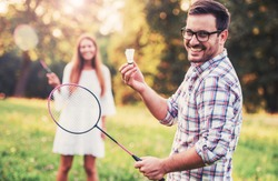 Young smiling couple playing badminton in the park and enjoying in moments of happiness. Sport, recreation, lifestyle, love concept