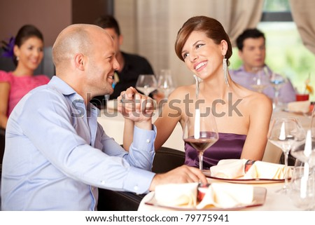 young smiling couple romancing at a restaurant table - stock photo