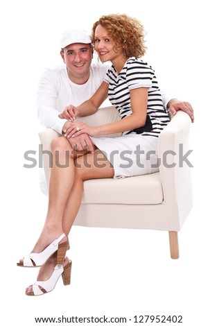 Young smiling couple sitting on armchair over white background