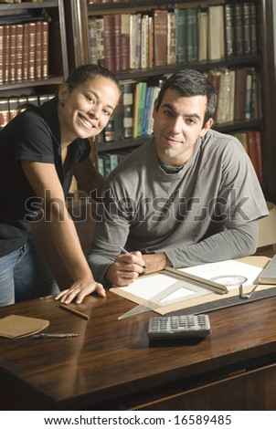 Young, smiling couple study together in an office with many books and a computer. Horizontally framed photo.