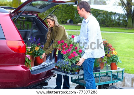 Young smiling couple with flowers near auto.