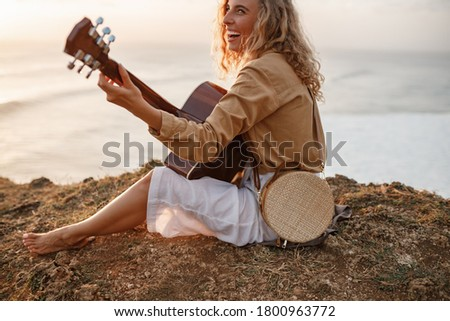 Young smiling curly hair woman sitting on the sand at a beach, playing acoustic guitar, looking away ストックフォト ©