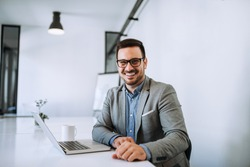 Young smiling entrepreneur in bright office working on laptop.