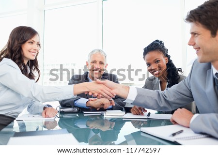 Young smiling executives shaking hands in front of their manager and a colleague - stock photo