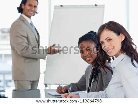 Young smiling executives sitting at the desk with a co-worker behind them