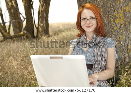 Young smiling fashion girl in glasses and notebook sitting near tree.