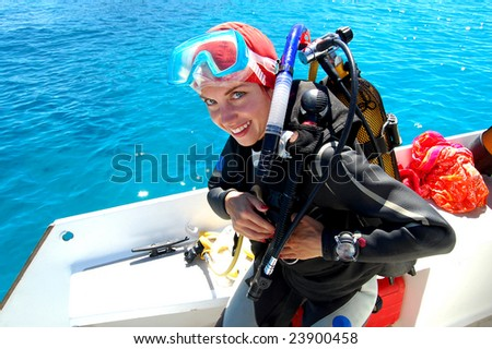 Young smiling female diver preparing for the dive