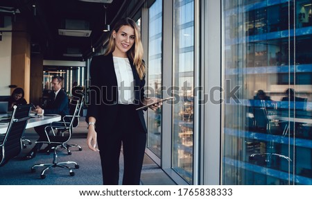 Young smiling female entrepreneur in elegant clothes browsing tablet while standing in  contemporary workplace on background of group of busy colleagues and looking at camera