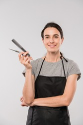 Young smiling female hairdresser holding hairbrush and scissors and looking at you over white background