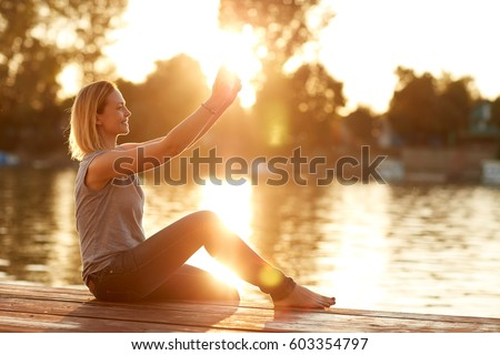 Young smiling female making selfie by the river at sunset - Shutterstock ID 603354797