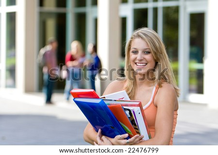 Young smiling female student carrying her books outside of school.  There are kids in the background. Horizontally framed photo.