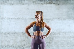 Young smiling fit attractive muscular sporty brunette in sportswear standing with hands on hips and looking away. Healthy lifestyle concept.
