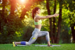 Young smiling fitness woman doing fitness exercises in the park on green grass. Fitness training outdoors. Fitness classes outdoors. Attractive fitness woman. Workout outdoors. Healthy lifestyle